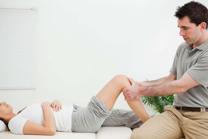 osteopath examining patients knee pain for osteopathy and rehabilitation treatment